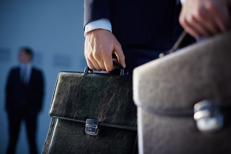 Foto de Cropped image of business partners carrying briefcases on the foreground while their colleague standing on the background  - Imagen libre de derechos