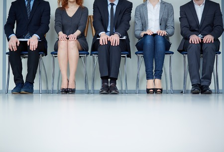 Several business people sitting on chairs in a row