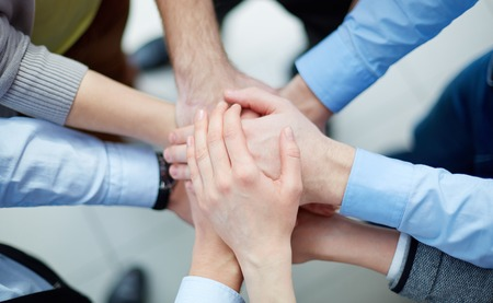 Photo for Above view of business partners making a pile of hands  - Royalty Free Image