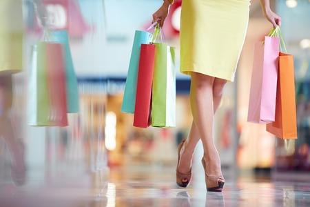 Foto de Legs of shopaholic with shopping bags walking down mall - Imagen libre de derechos