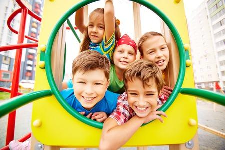 Photo pour Image of joyful friends having fun on playground outdoors  - image libre de droit