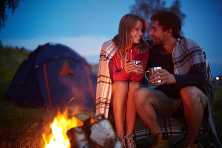 Photo for Young couple sitting by the fire and drinking tea outside - Royalty Free Image