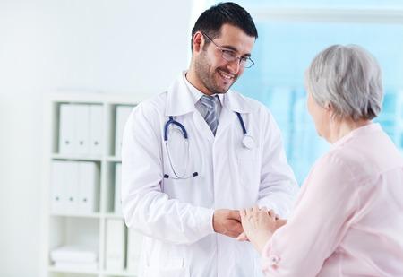 Foto de Confident doctor looking at his senior patient while speaking to her - Imagen libre de derechos