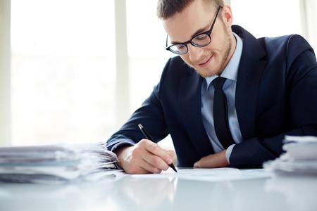 Foto de Portrait of handsome office worker making notes - Imagen libre de derechos