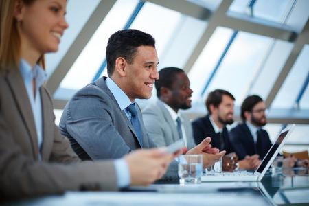 Foto de Row of business people listening to presentation at seminar with focus on elegant young man - Imagen libre de derechos