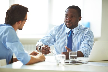Photo pour Image of two young businessmen interacting at meeting in office - image libre de droit