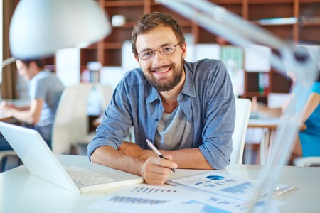 Photo for Handsome businessman in casual working in office on background of his partners - Royalty Free Image