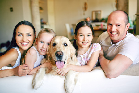 A young friendly family of four with pet looking at camera at home