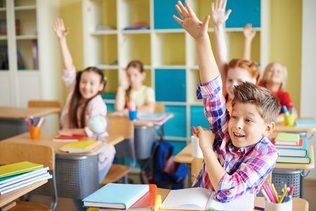 Photo pour Portrait of cute boy raising hand at workplace with his classmates behind - image libre de droit