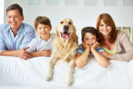 Photo pour Smiling family of four with a dog - image libre de droit