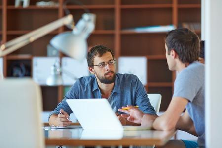 Foto de Two businessmen interacting at meeting in office - Imagen libre de derechos