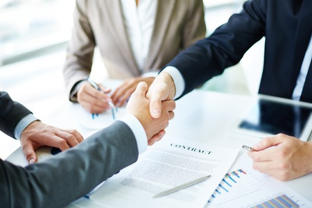 Photo pour Image of business partners handshaking over business objects on workplace - image libre de droit