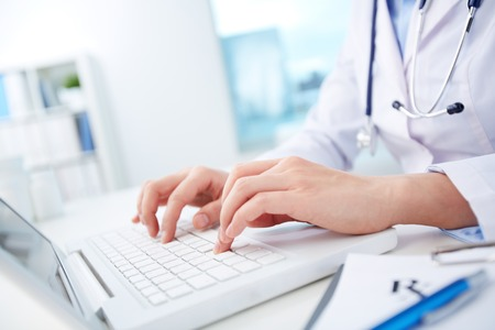 Photo pour Close-up of hands of a nurse typing on laptop - image libre de droit