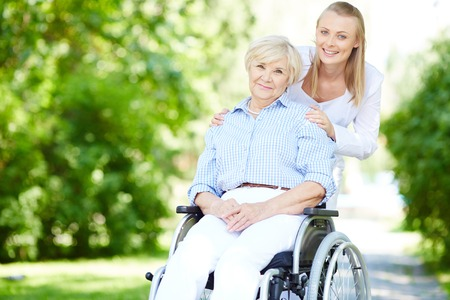 Photo for Female caregiver and senior patient in a wheelchair looking at camera outside - Royalty Free Image