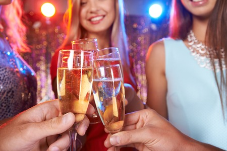 Photo pour Hands of friends cheering up with champagne at party - image libre de droit
