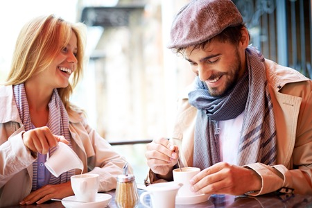 Foto de Portrait of affectionate couple in stylish clothes having coffee in cafe - Imagen libre de derechos