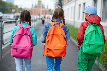 Foto de Backs of schoolkids with colorful rucksacks moving in the street - Imagen libre de derechos