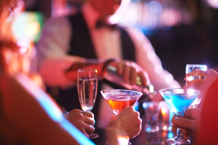Hands of young people holding martini and champagne in the bar