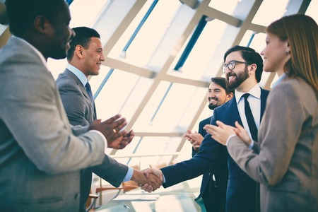 Group of business people congratulating their handshaking colleagues after signing contract