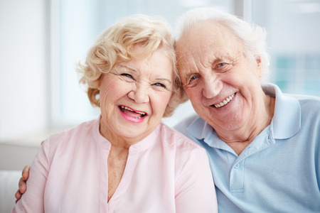 Photo pour Portrait of a positive senior couple looking at camera and smiling - image libre de droit