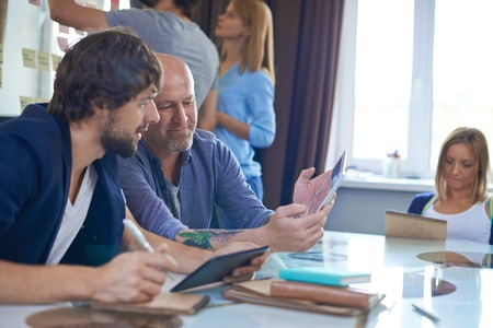 Foto de Mature businessman with touchpad showing his colleague ideas for new project - Imagen libre de derechos