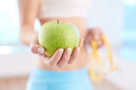 Photo pour Close-up of fresh green apple held by a woman - image libre de droit