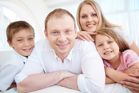 Portrait of happy parents and their children looking at camera with smiles