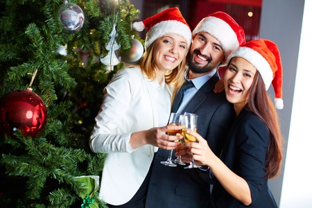 Foto de Friendly co-workers in Santa caps toasting with champagne by Christmas tree in office - Imagen libre de derechos