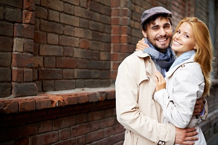 Portrait of smiling couple in stylish trench-coats looking at camera outside