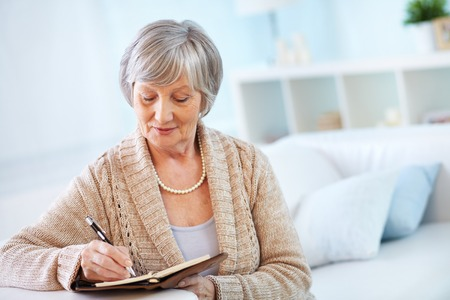 Foto per Senior woman making notes in notepad - Immagine Royalty Free
