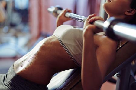 Photo pour Woman lifting weights in gym - image libre de droit