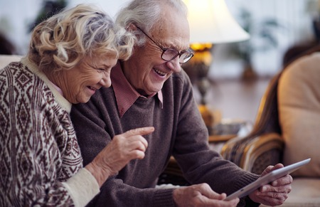 Photo pour Elderly husband and wife using digital tablet at home - image libre de droit