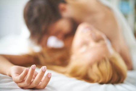 Photo for Couple kissing passionately in bed - Royalty Free Image