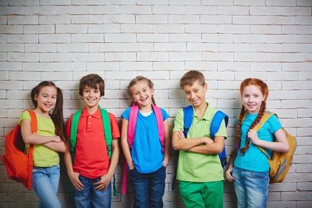 Foto de Group of cute school friends in casualwear looking at camera - Imagen libre de derechos