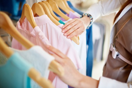 Foto de Young woman looking through new clothes during shopping - Imagen libre de derechos