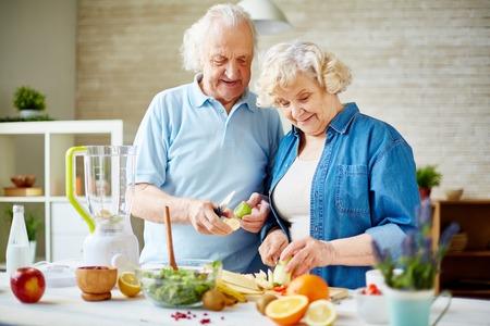 Photo pour Modern senior couple preparing fresh fruits for making smoothie - image libre de droit