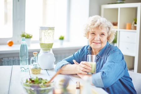 Photo for Happy senior female with glass of fruit smoothie looking at camera - Royalty Free Image