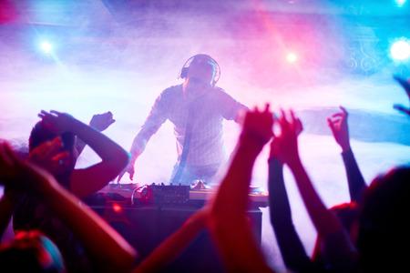 Photo pour Charismatic disc jockey at the turntable - image libre de droit