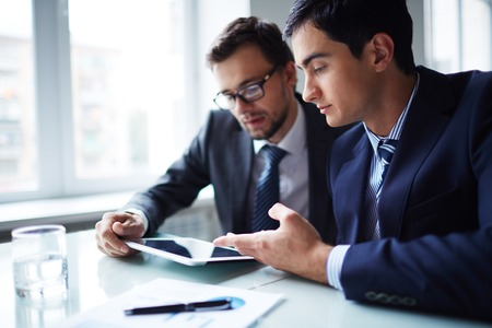 Foto de Two businessmen working with touchpad at meeting in office - Imagen libre de derechos
