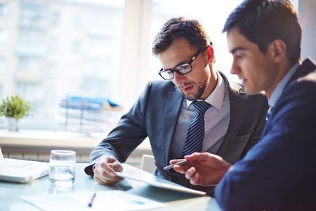Photo pour Serious businessman listening to his colleague explanations at meeting - image libre de droit