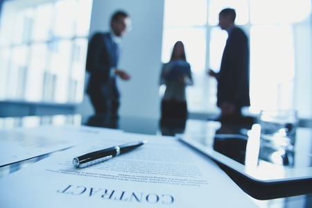 Photo pour Close-up of contract with business people in the background - image libre de droit