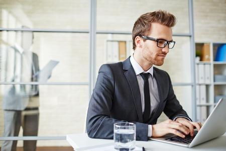 Foto de Young businessman in formalwear typing on laptop - Imagen libre de derechos