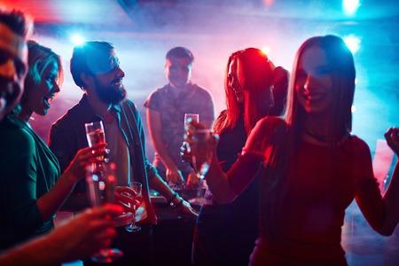 Photo pour Happy friends toasting at night party - image libre de droit