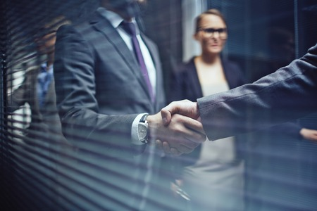 Foto de Close-up of businessmen handshaking on background of woman - Imagen libre de derechos