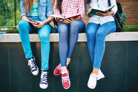 Photo for Modern teen girls reading outside - Royalty Free Image