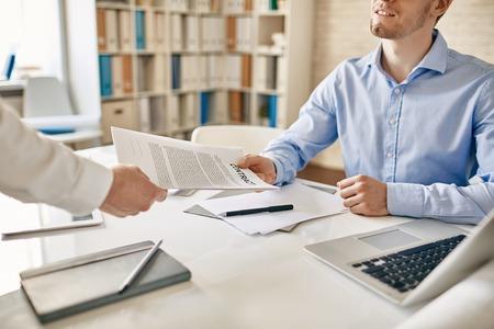 Foto de Businessman his colleague giving contract to read and sign - Imagen libre de derechos