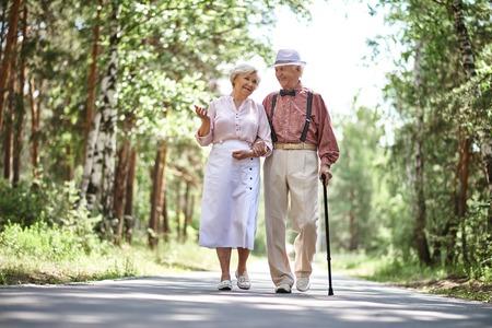 Photo pour Portrait of happy senior couple walking in park - image libre de droit