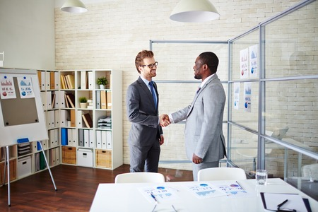 Confident managers handshaking in office after signing contract