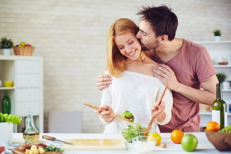 Foto de Young man kissing his wife while she mixing up salad ingredients - Imagen libre de derechos