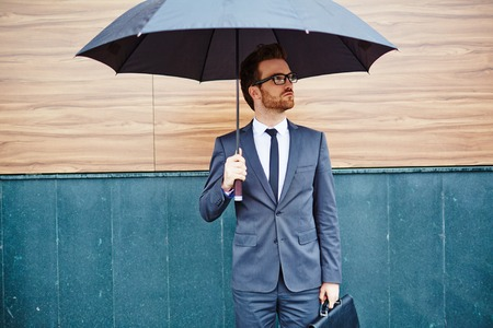 Foto de Young entrepreneur with briefcase standing outside under umbrella - Imagen libre de derechos